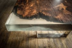Detail of clear cast resin table with wood and metal legs.