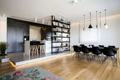 This raised and light platform helps to delineate the kitchen from the dining room in this urban luxury penthouse apartment