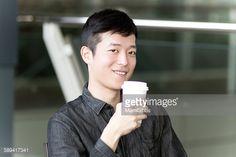 ストックフォト : Young man is smiling and drinking coffee