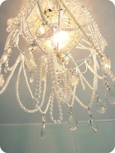 DIY chandelier made from a dollar store hanging basket, and thrift store beads and necklaces.