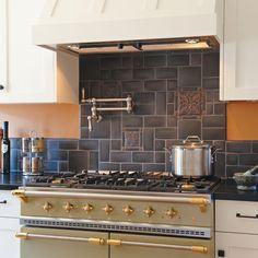 Motawi Tileworks click thru to medieval animal kitchen-white cabinets, red tile backsplash