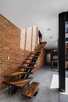 Floating wood and steel staircase set against a brick wall backdrop