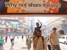 Why Don't You Share The Joy (with Khushi pointing to the sign - Khushi means Joy)