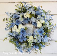 This silk floral wreath features premium pale blue delphiniums, darling sky blue and periwinkle blue forget-me-nots, icy white ranunculus blooms and sparkling white pips surrounded by spring green latex eucalyptus. The wreath has been sprayed with matte acrylic for lasting beauty and could make a wonderful outdoor wreath protected from the elements, as well as a lovely candle ring or centerpiece. Only industrial strength adhesive is used for lasting durability and only premium - top quality…