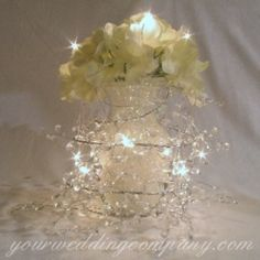 Place these beautiful ice drop garlands around the base of your cake or combine with tulle draping on banisters or pew ends. Bend to form a wreath or decorate your gift or guestbook table. Each garland measures 5 feet long with additional 9 inches of silver wire. Garland Lights Centerpiece - www.yourweddingcompany.com
