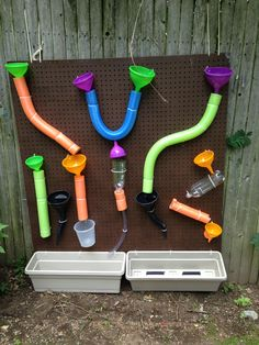 do it yourself water wall made from peg board, dollar store  pool noodles, funnels, bottles and planters.