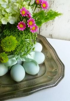 Spoons are bend at a right angle and mounted around a cylinder for the flowers. Then dyed eggs are held in the spoon. So cute.