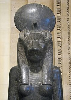 "Louvre Museum - Statue of the goddess Sekhmet. This colossal seated statue represents the goddess Sekhmet, ""the powerful"". Mane and hair meld together harmoniously beneath the solar disk and uraeus-cobra. A carved inscription on the front of the seat refers to ""Amenophis III, beloved of the goddess"""