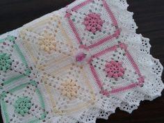 Manta de Crochê feita de lã com quadrados coloridos. <br>Destaque: Quadros coloridos com flores em ponto pipoca. <br>Medida: 1 m X 1 m. <br>Pode ser feita em qualquer cor basta colocá-las na caixa de diálogo.