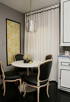 The contrast of the modern tulip table with the black leather traditional French chairs is unexpected, but it works.  In a small space, as well!