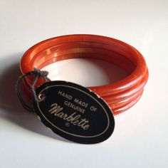"Four simple phenolic (Bakelite) bangles with their original ""Hand made of Genuine Marblette"" hang-tag. Once the Bakelite Corporation patent ran out, Marblette and a variety of other companies (including the Catalin corporation) began producing phenolic resin products, each with their own special tweak in formula. All American-made phenolic resin items from the original 1909-1940s period are considered Bakelite, as a generic term, regardless of manufacturer. (Hang-tags are so cool!)"
