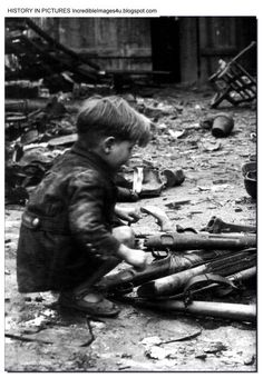 A German boy plays with guns among the debris