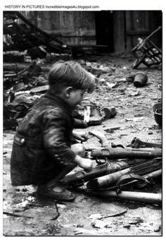 A German boy plays with guns among the debris