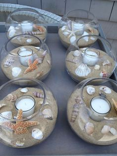 DIY beach themed Wedding Table Center Pieces - seashells, sand, tea light candles, glass bowls - maybe some colored ribbon?