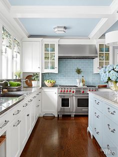 Abundant lower drawers with brushed silver handles more than compensate for the lack of upper cabinets in this spacious kitchen.A light color palette and glass-front doors keep the room bright and airy. Mixing blue and white cabinetry conveys classic cottage style.