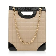 This classic Chanel tote is made from supple beige quilted lambskin with black patent leather trim and brushed gold-tone hardware. Details include two cut out handles, two woven chain shoulder straps, and an open top. The interior is fully lined with one open pocket and one zippered pocket.