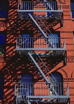 Fire escape - Typical American-style fire escapes in a street of SoHo, Manhattan, New York City. As building codes became more common in countries around the turn of the 20th century, fire safety became an important concern for new construction. Building owners were increasingly required to provide adequate escape routes, and at the time, fire escapes seemed the best option available. Not only could they be included in new construction at a low cost