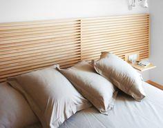 Imagen del cabecero de madera con las mesillas e interruptores integrados. Diseño y reforma de 08023 Arquitectos - Barcelona