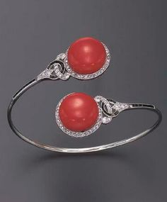 AN ART DECO CORAL, DIAMOND AND ONYX BANGLE BRACELET Of crossover design, each cabochon coral terminal, within a rose-cut diamond frame, joined by openwork calibré-cut onyx, old European, single and rose-cut diamond shoulders to the slender white gold band, mounted in white gold, (two onyx deficient), circa 1920, 2 3/8 ins. diameter