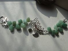 "green aventurine and leaf details makes this bracelet stand out! A chubby bird charm and emerald ""egg"" dangle from the leaves $21"