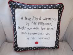 "With a touching message about friends, this hand-embroidered pillow is lined in black floral calico & red piping. A bright red button is centered on the 14"" square pillow."