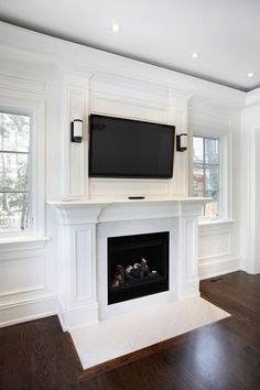 This wooden mantle, with a marble hearth, are a brilliant white color for a modern touch on a fireplace. The TV creates the perfect middle ground for modern and luxurious decor.