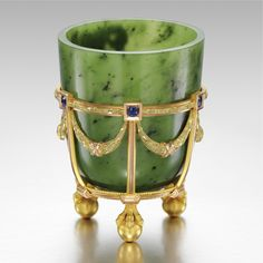 A Fabergé jewelled gold-mounted nephrite vase, workmaster: Michael Perchin, St. Petersburg, circa 1890 The ovoid body on a gold stand with three ball and claw feet, the neo-classical cagework mount applied with ribbon tied laurel garlands set with six sapphires,