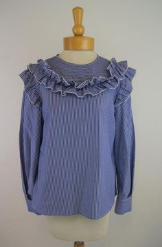 This blue and white pinstriped blouse has a round neck, long sleeves, and ruffled trim. Tara Jarmon, Ruffles, The Selection, Ruffle Blouse, Blue And White, Blouses, Long Sleeve, Sleeves, Cotton