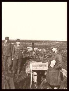 """Stalingrad, 1942. """"Vor dem provisorischen Bunker einer Funkerabteilung auf der Höhe 107,5 positionieren sich für das Erinnerungsfoto ein Truppführer und zwei seiner Männer."""""""