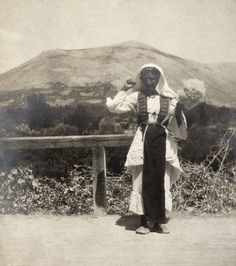 A Bulgarian woman in traditional clothing spins wool as she walks.  Location:Macedonia.