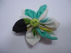 Jolie barrette en coton dans les tons noir, vert, jaune et blanc, en forme de fleur, avec un coeur en bouton vert. La barrette est une pince crocodile noire de 3.3 cm.  Tarifs : 4€ + fdp