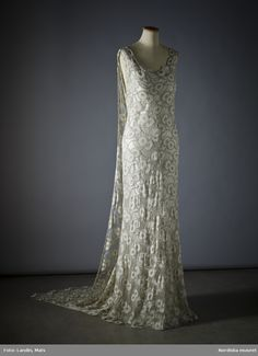 Dress of light green peau d'specify with silver flowers. Worn by Queen Astrid of Belgium at the Princess Ingrid's wedding in Stockholm 1935. Made in Paris with Irène Dana. Nordic Museum Inv No 206,293th