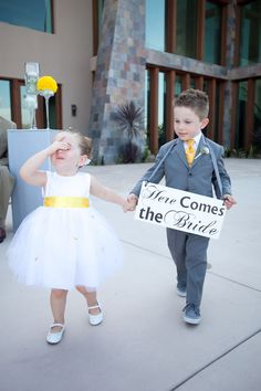 Cute little girl in tulle dress with yellow sash and boy in gray suit with yellow tie - Photo by April Smith & Co.