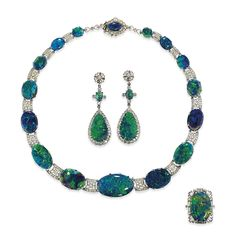 AN ART DECO BLACK OPAL AND DIAMOND PARURE Comprising a necklace, ear pendants and ring, the necklace designed as a series of polished opal panels interspersed with millegrain-set circular-cut diamond openwork links to the similarly-set cluster clasp, together with earrings of matching design and oval opal panel ring with geometric baguette-cut diamond surround, circa 1930   Christie's