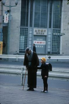 A man solemnly pauses before a shrine while taking his son to school, Tokyo, Japan, 1961, photograph by Burt Glinn.