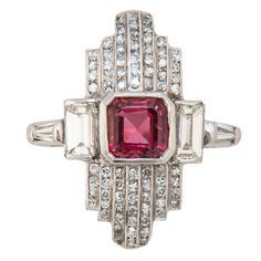Art Deco Natural Spinel Diamond Ring. Circa 1930s Platinum Diamond and Spinel Ring, Centrally set with a Fine Natural Red Stepped Cut Spinel approximately 1 Carat. Further set with Baguette and single cut Diamonds totaling 1 carat. Shank containing Markers Numbers. c 1930s