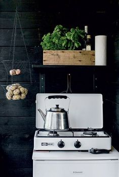 create contrast by painting the walls a midnight hue the appliances really stand out. The floating shelf in the same color stores olive oils and fresh veggies right at hand. The hanging wire basket and old stovetop create a rustic vibe– the perfect for a vacation retreat.