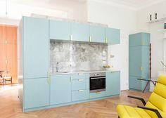 Le studioNimtim a rénové un appartement à l'ouest de Londres comprenant une cuisine habillée de marbre et de bleu pastel, un parquet en zigzag et du mobil