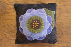 This is a Pincushion that is handmade by Lisa Bongean herself.  This one is Posey   Lisa used her own hand dyed wools for this flower