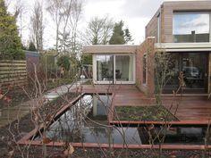 Particuliere tuin met strakke vijver en hardhouten terras.