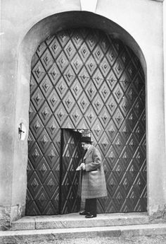 Swedish sculptor Carl Milles opening the elaborate door to his home. Photograph by Alfred Eisenstaedt. Stockholm, Sweden, 1934.