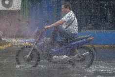 2. August: Ein Mann fährt in Manila, Philippinen, auf einer überfluteten… …