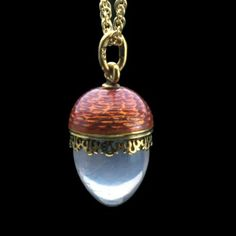 A Faberge miniature egg pendant, with deep pink enamel to top, edged with a yellow gold fringe in scroll design, mounted with polished rose quartz below, workmaster Erik Kollin, St Petersburg 1896-1901.