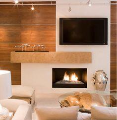Bastante original, esta opção desalinhou a TV da lareira , o volume criado no meio organizou os espaços.