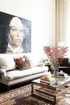 Living room with hung portrait over a white couch, glass coffee table and stacked books.