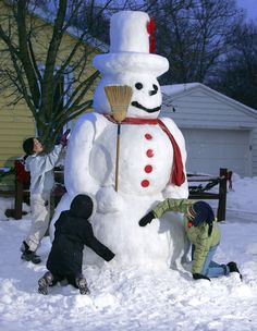 Patty Lesatz, right, her daughter, Kristina, 9, and neighborhood friend, Rebbeca Luce, 10, left, pack new snow on their ten-foot-tall snowman in the front yard of their home in Grand Rapids, Michigan.