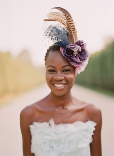 a large fascinator with flowers and feathers