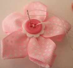 Flower-making with ribbons. Maybe sew this onto a baby blanket or teddy bear for children.
