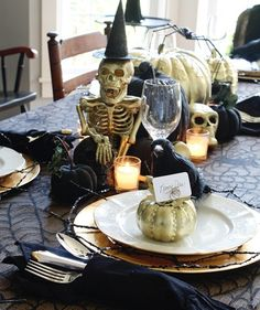 Ditch the usual orange and black color scheme for something a little more sophisticated, like this black and gold table. The tablecloth is made from burlap layered with black lace from a fabric store. For each place setting, a gold charger is topped with a black sparkly cobweb decoration, a white plate, and a gold pumpkin place card holder. And the centerpiece is a grouping of gold and black painted pumpkins with a gold skeleton and skulls.