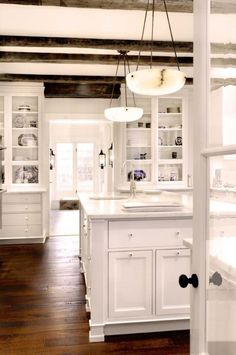 White elegant rustic farmhouse kitchen. Beams, white and hardwood floors.